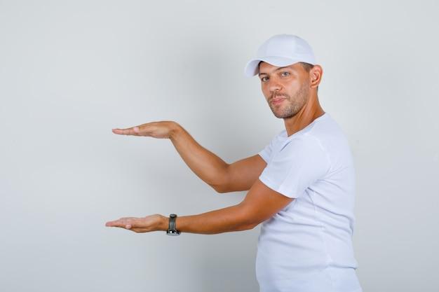 Молодой человек показывает знак размера руками в белой футболке, кепке, вид спереди.