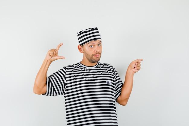縞模様のtシャツ、帽子で脇を指して、小さなサイズのサインを示す若い男。