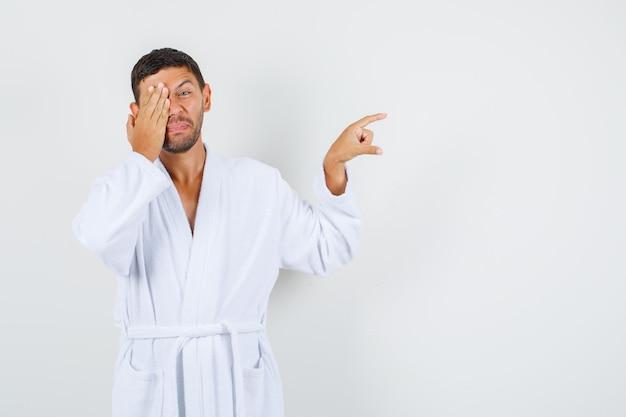 白いバスローブの正面図で目を手に小さなサイズを示す若い男。