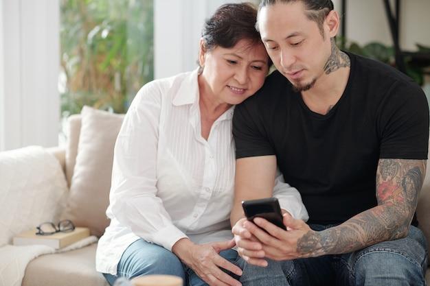 彼らが自宅のソファに座っている間、彼の成熟した母親に彼の携帯電話で何かを見せている若い男
