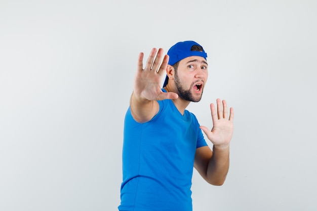 Young man showing stop gesture in blue t-shirt and cap and looking scared