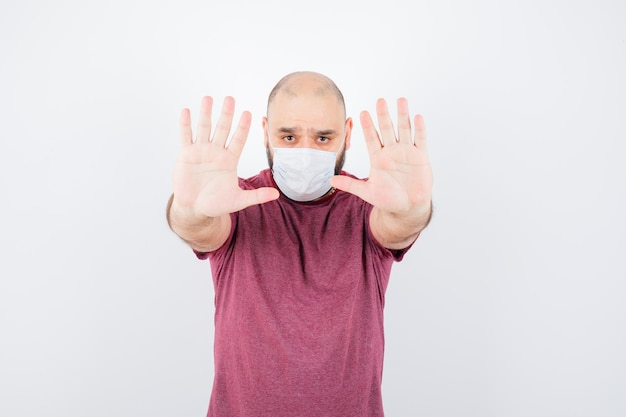 분홍색 티셔츠와 마스크를 쓰고 진지한 표정을 짓고 있는 청년.