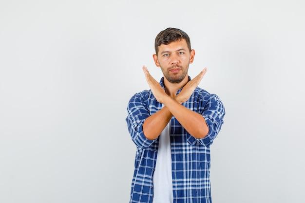 Молодой человек показывает жест стоп в рубашке и выглядит уверенно. передний план.