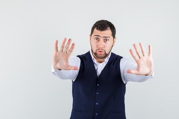 Молодой человек показывает жест остановки в рубашке и жилете и выглядит испуганным, вид спереди.