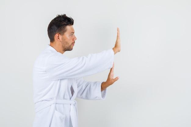 白いバスローブで停止ジェスチャーを示し、静かに見える若い男。