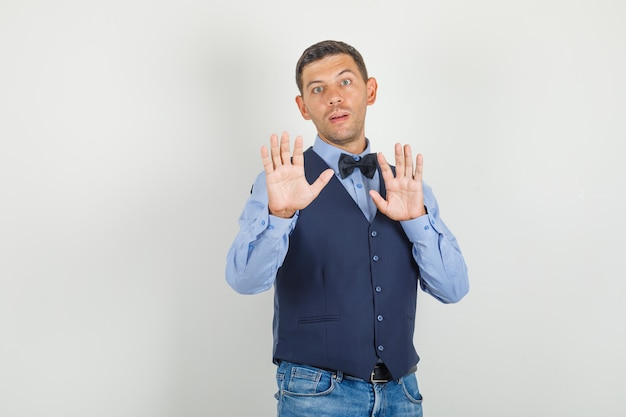 Young man showing stop gesture in suit, jeans