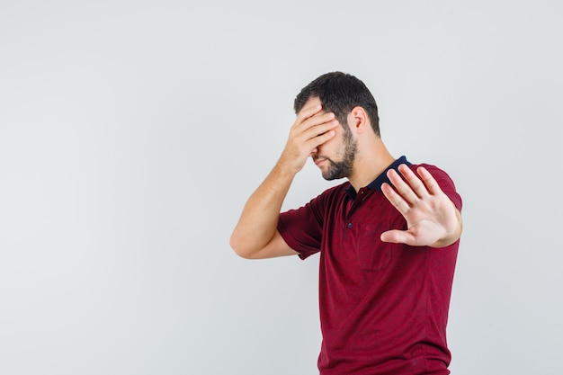 Young man showing stop gesture while closing eyes in red t-shirt and looking uncomfortable. front view.