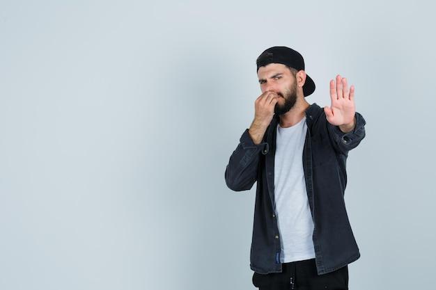 Молодой человек показывает жест стоп, прикрывая нос