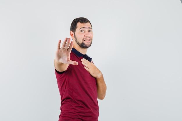 Молодой человек показывает жест стоп, держа руку на груди в красной футболке и выглядит взволнованным. передний план.