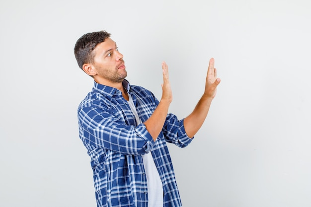 Young man showing stop gesture while looking to side in shirt and looking scared. front view.