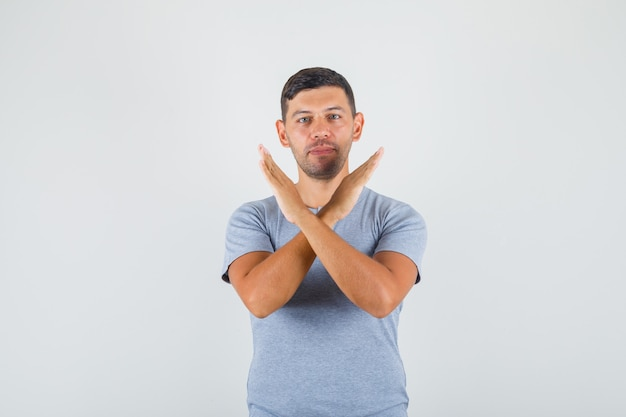 Young man showing stop gesture with crossing hands in grey t-shirt and looking confident.