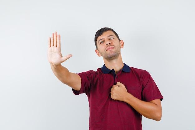 Giovane che mostra il gesto di arresto con il pugno sul petto in maglietta e sembra educato. vista frontale.