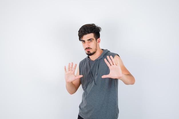 灰色のtシャツで一時停止の標識を示し、真剣に見える若い男