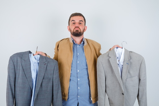 Young man showing suits in jacket, shirt and looking wistful , front view.