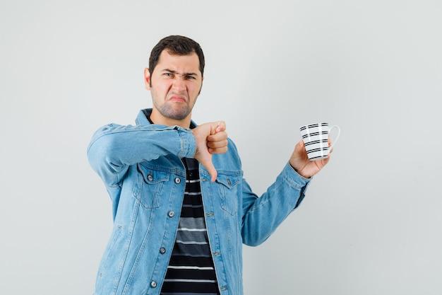 Молодой человек показывает палец вниз, держит чашку напитка в футболке, куртке и выглядит недовольным. передний план.