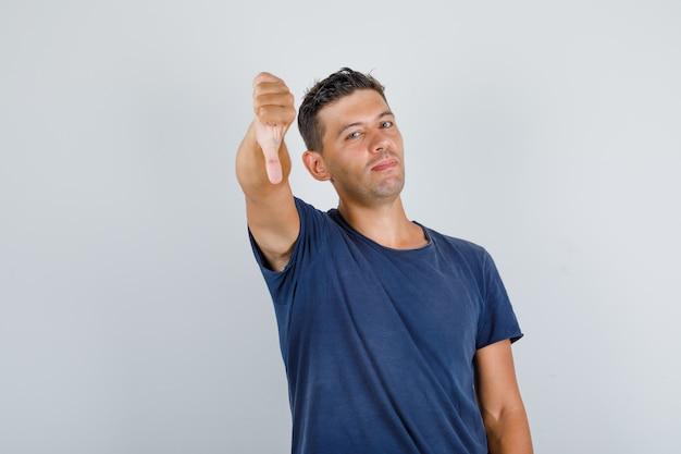 Молодой человек показывает палец вниз в темно-синей футболке и выглядит недовольным, вид спереди.
