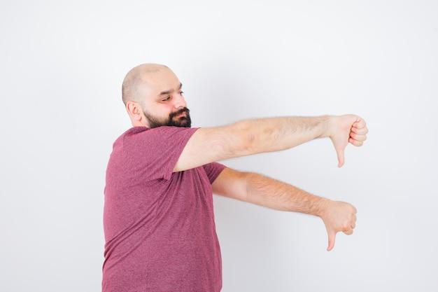 ピンクのtシャツで親指を下に見せて不満を探している若い男。 。