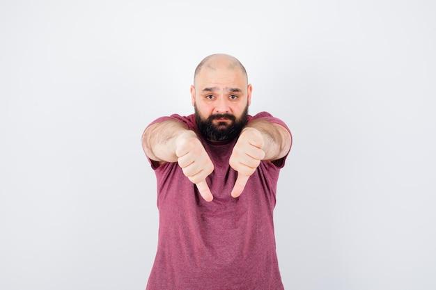 ピンクのtシャツで親指を下に見せて、不機嫌そうに見える若い男。正面図。