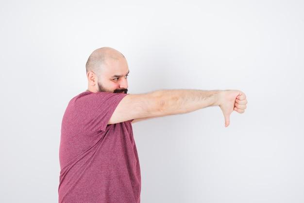 ピンクのtシャツで親指を下に見せて不満を探している若い男。