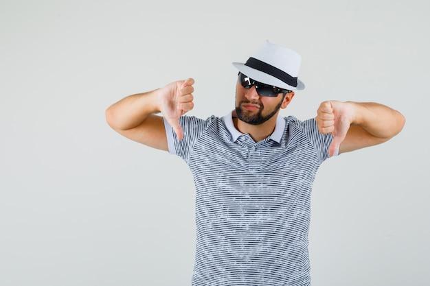 젊은 남자 t- 셔츠, 선글라스 아래로 엄지 손가락을 보여주는 불쾌 하 게 찾고. 전면보기.