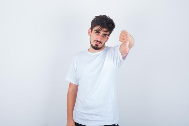 白いtシャツで親指を下に見せて自信を持って見える若い男