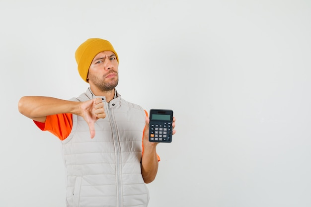 Young man showing thumb down while holding calculator in t-shirt, jacket, hat and looking dissatisfied.