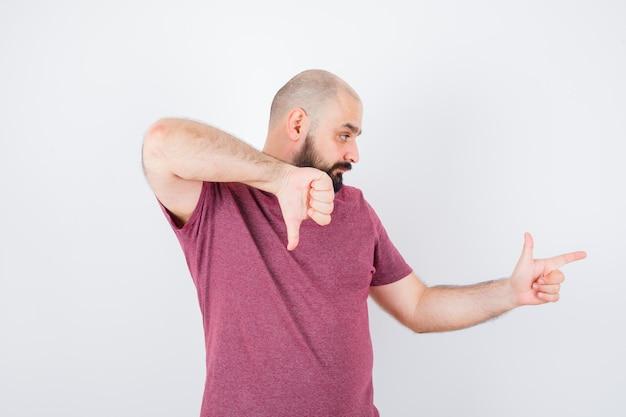 ピンクのtシャツの正面図で脇を指して親指を下に見せている若い男。