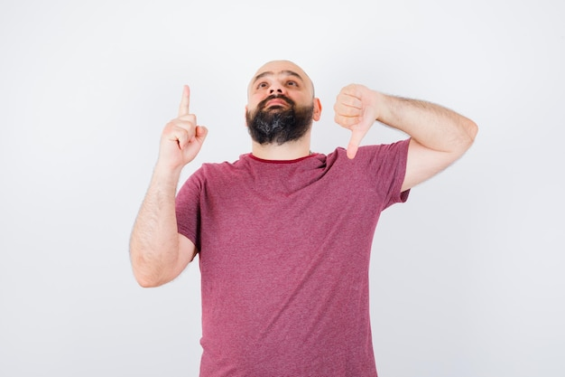 분홍색 티셔츠를 입고 정면을 가리키며 엄지손가락을 아래로 내리는 젊은 남자.