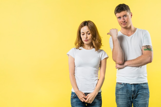 Young man showing thumb up to her sad girlfriend standing against yellow background