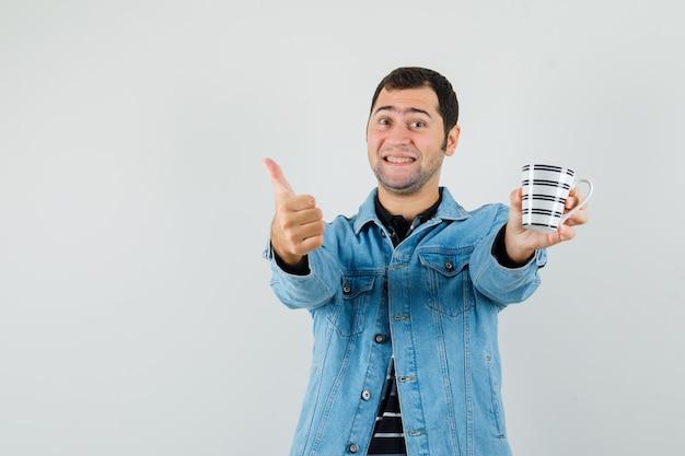 엄지 손가락을 보여주는 젊은 남자, 티셔츠, 재킷에 음료 잔을 들고 쾌활한, 전면보기를 찾고.