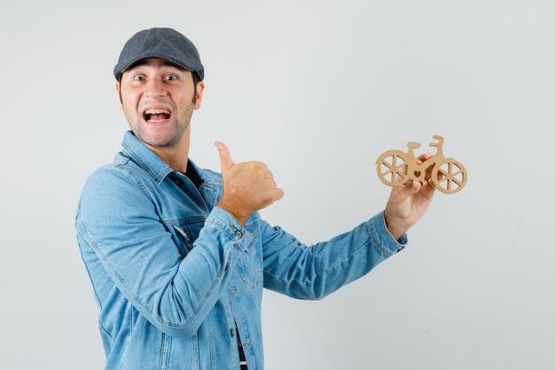 親指を立てて、tシャツ、ジャケット、キャップで木のおもちゃの自転車を持って、幸せそうに見える若い男。正面図。