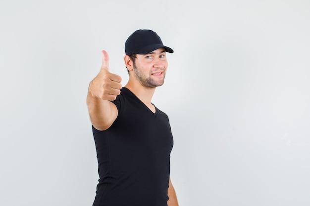 黒のtシャツ、キャップで親指を表示し、陽気に見える若い男。