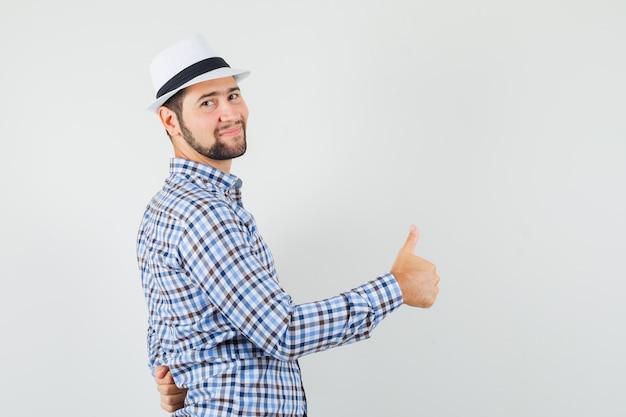 Молодой человек показывает палец вверх в проверенной рубашке, шляпе и выглядит весело. .