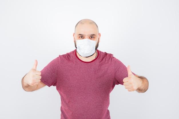분홍색 티셔츠, 마스크를 쓰고 긍정적인 모습을 보이는 젊은 남자.