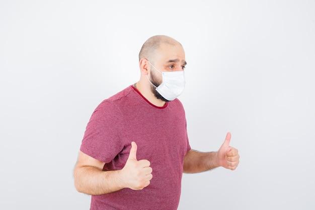 분홍색 티셔츠, 마스크를 쓰고 엄지손가락을 치켜드는 청년.