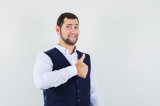 シャツとベストで親指を表示し、陽気な見ている若い男