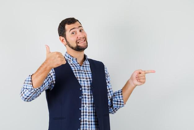 Молодой человек показывает большой палец вверх, указывая в сторону в рубашке, жилете и выглядит весело.