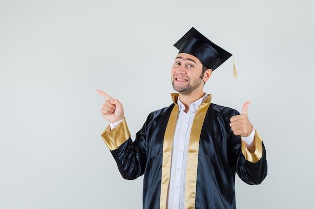 Молодой человек показывает палец вверх, указывая вверх в униформе выпускника и рад, вид спереди.