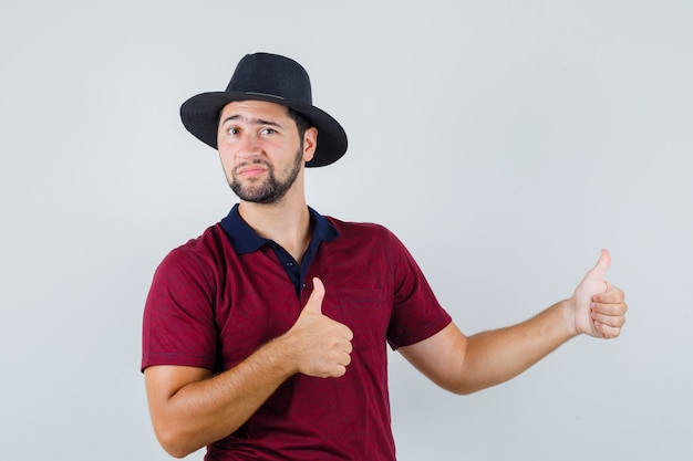 Young man showing thumb up at side in red t-shirt,hat and looking confident , front view.