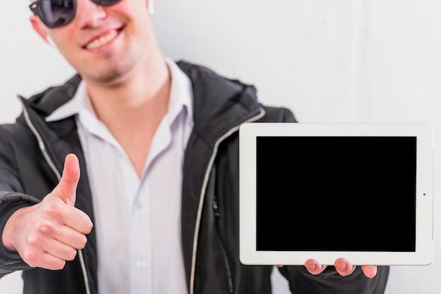 Young man showing thumb up sign holding digital tablet in hand