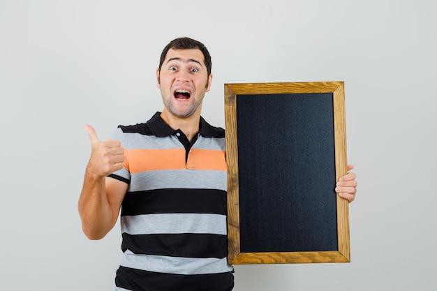 Tシャツに黒いフレームを保持し、陽気に見えながら親指を表示する若い男。正面図。
