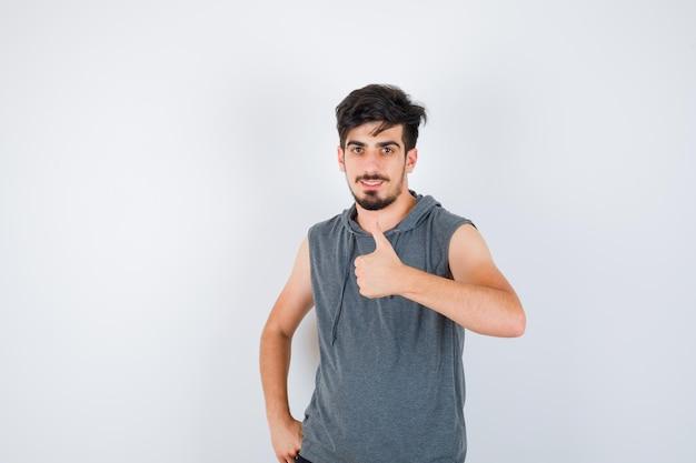 灰色のtシャツを着て腰に手を握り、真剣に見ながら親指を上に表示する若い男