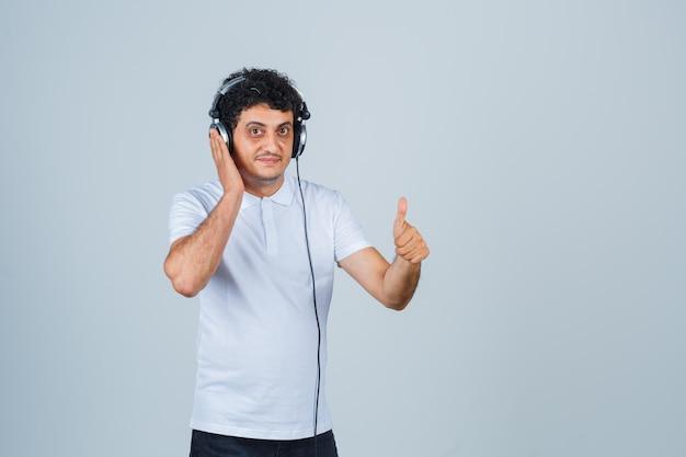 白いtシャツで音楽を聴き、自信を持って見ながら親指を立てて若い男。正面図。