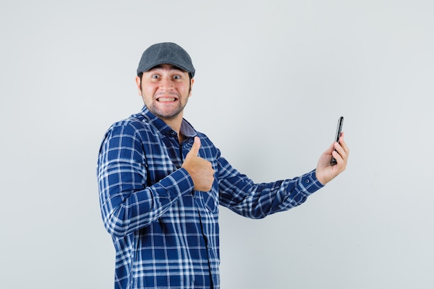 Young man showing thumb up while making video call in shirt, cap and looking glad , front view.