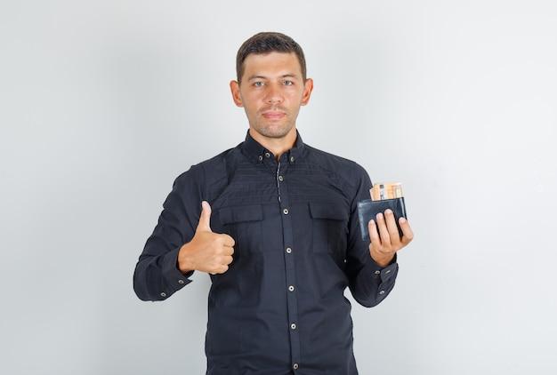Молодой человек показывает палец вверх с бумажником в черной рубашке и выглядит счастливым