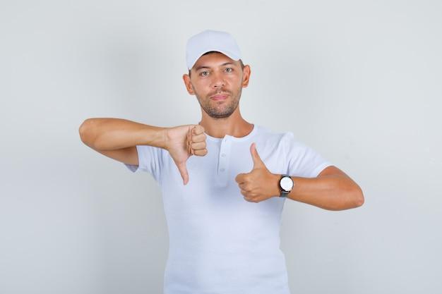 Молодой человек показывает большие пальцы руки вниз и вверх в белой футболке, вид спереди кепки.