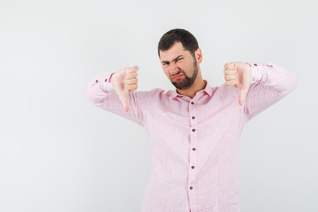 Молодой человек показывает палец вниз в розовой рубашке и выглядит разочарованным