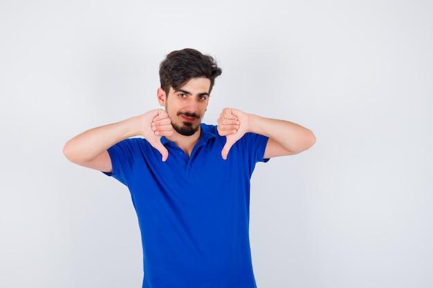 Молодой человек показывает палец вниз обеими руками в синей футболке и выглядит оптимистично