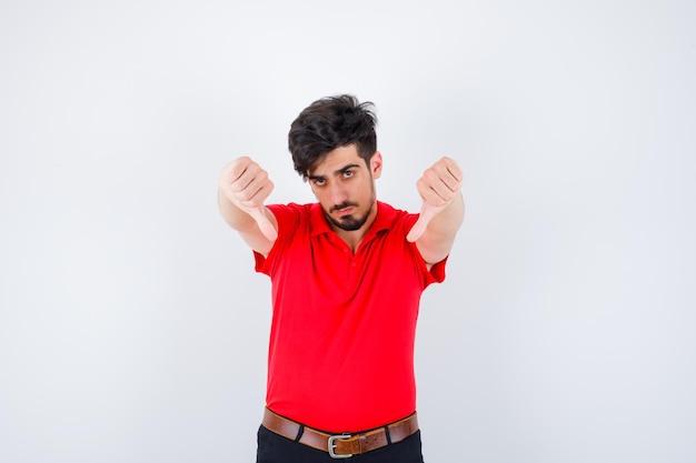 Молодой человек в красной футболке показывает большие пальцы вниз указательными пальцами и выглядит серьезно