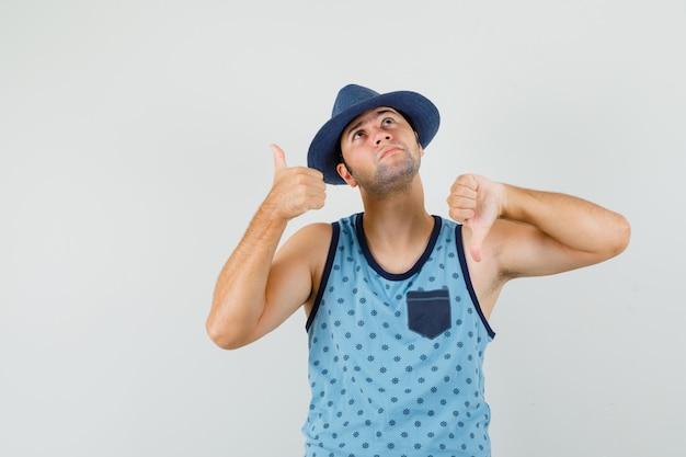 青い一重項、帽子、物思いにふけるように親指を上下に示す若い男。正面図。